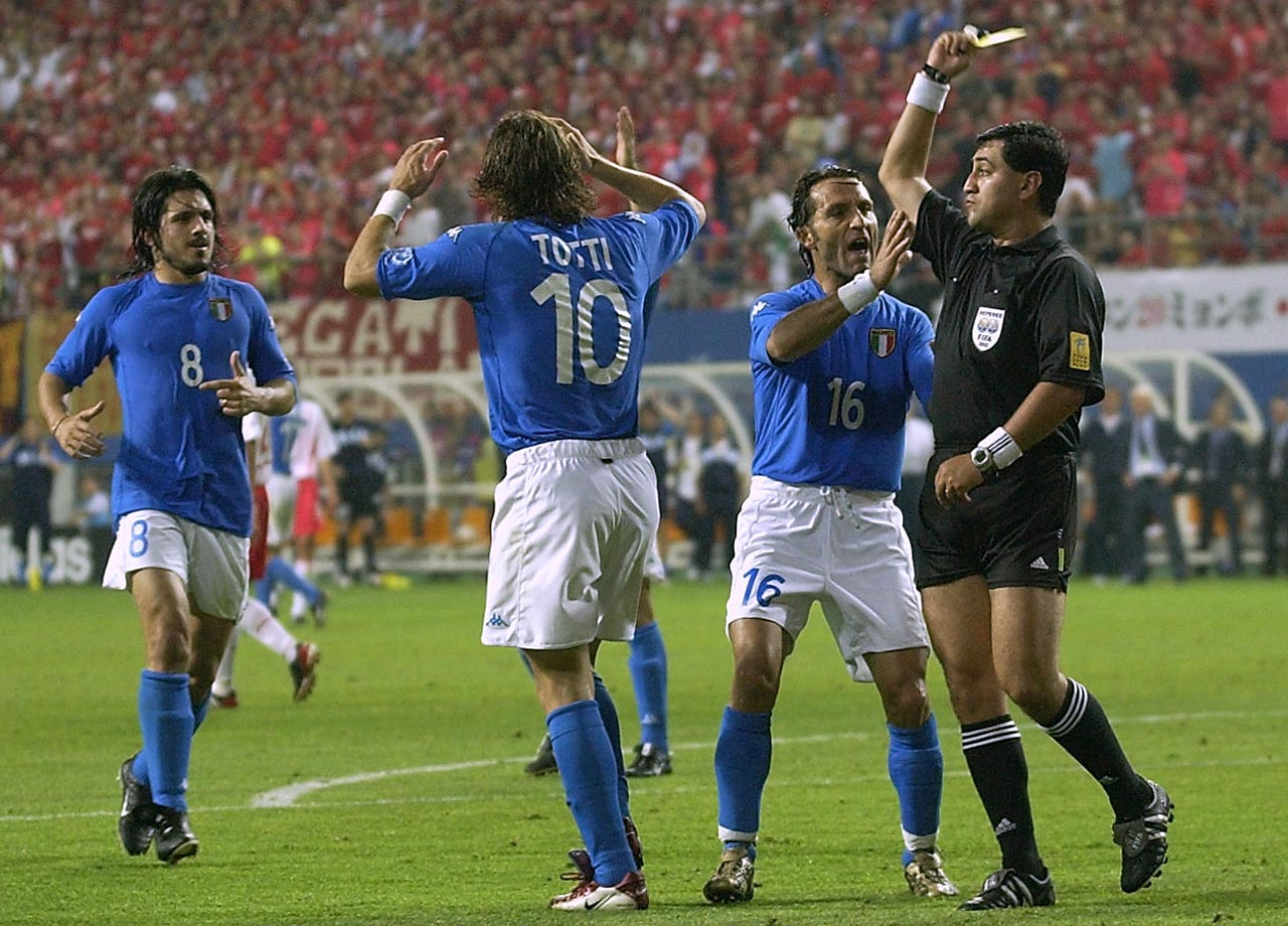 Francesco Totti walks away in disgust after being awarded a controversial second yellow card in Italy's second-round match with hosts South Korea in the 2002 World Cup as his teammates protest to the referee.  South Korea went on to beat Italy, and Spain in the following match, fueling talk of bribery on the part of the South Koreans.