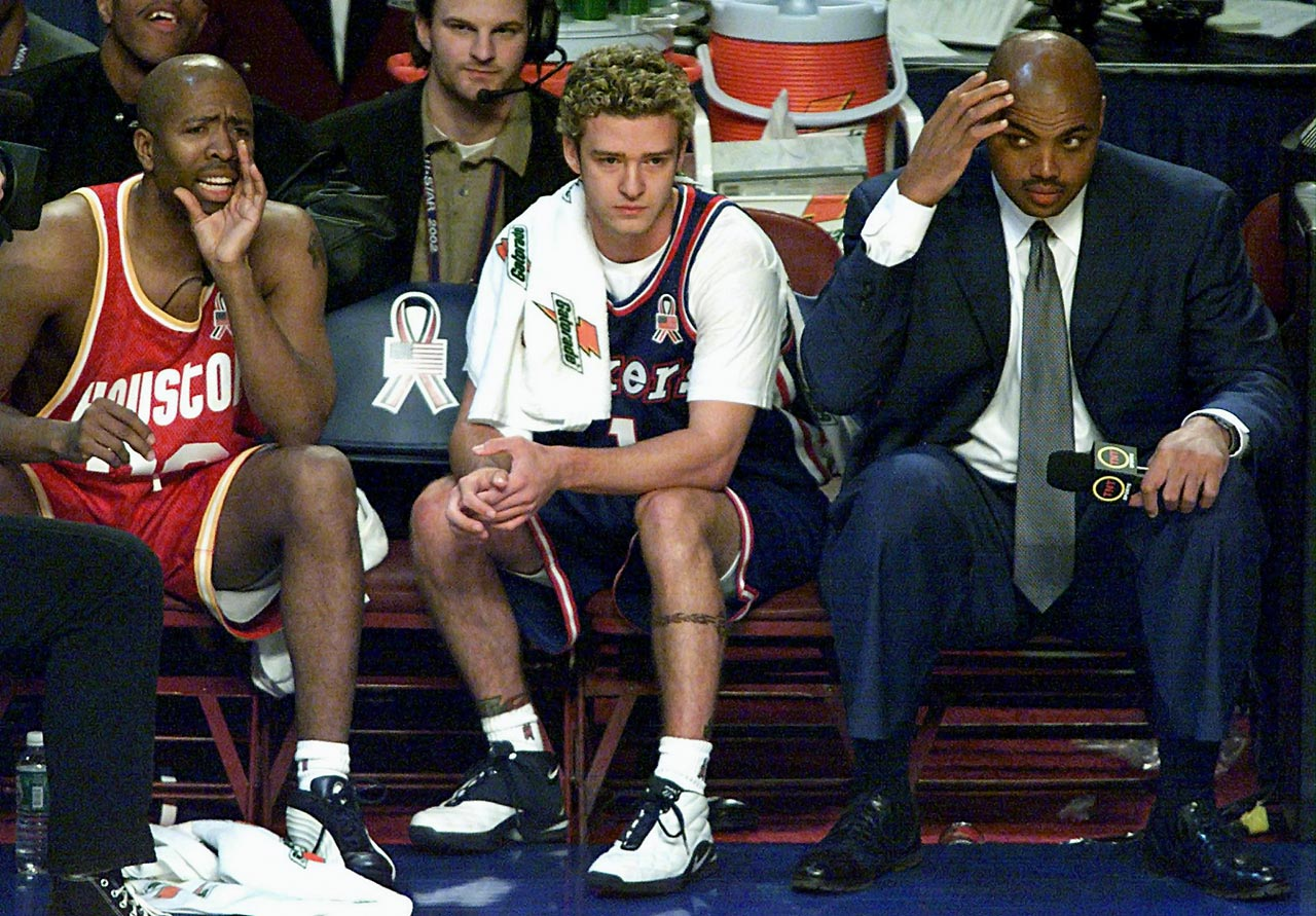 Kenny Smith yells out to his teammates as Justin Timberlake and Charles Barkley look on during a Hoop It Up 4-on-4 competition before the NBA All-Star Game in Philadelphia on Feb. 9, 2002.