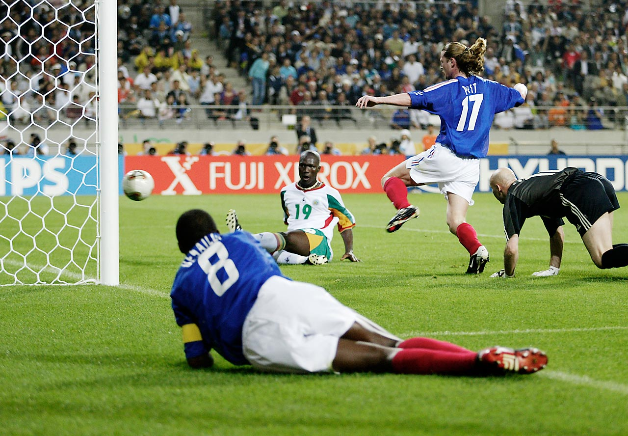 Papa Bouba Diop of Senegal scores the winning goal against France and goalkeeper Fabien Barthez in the 2002 World Cup. Emmanuel Petit and a ground Marcel Desailly of France look on helplessly.