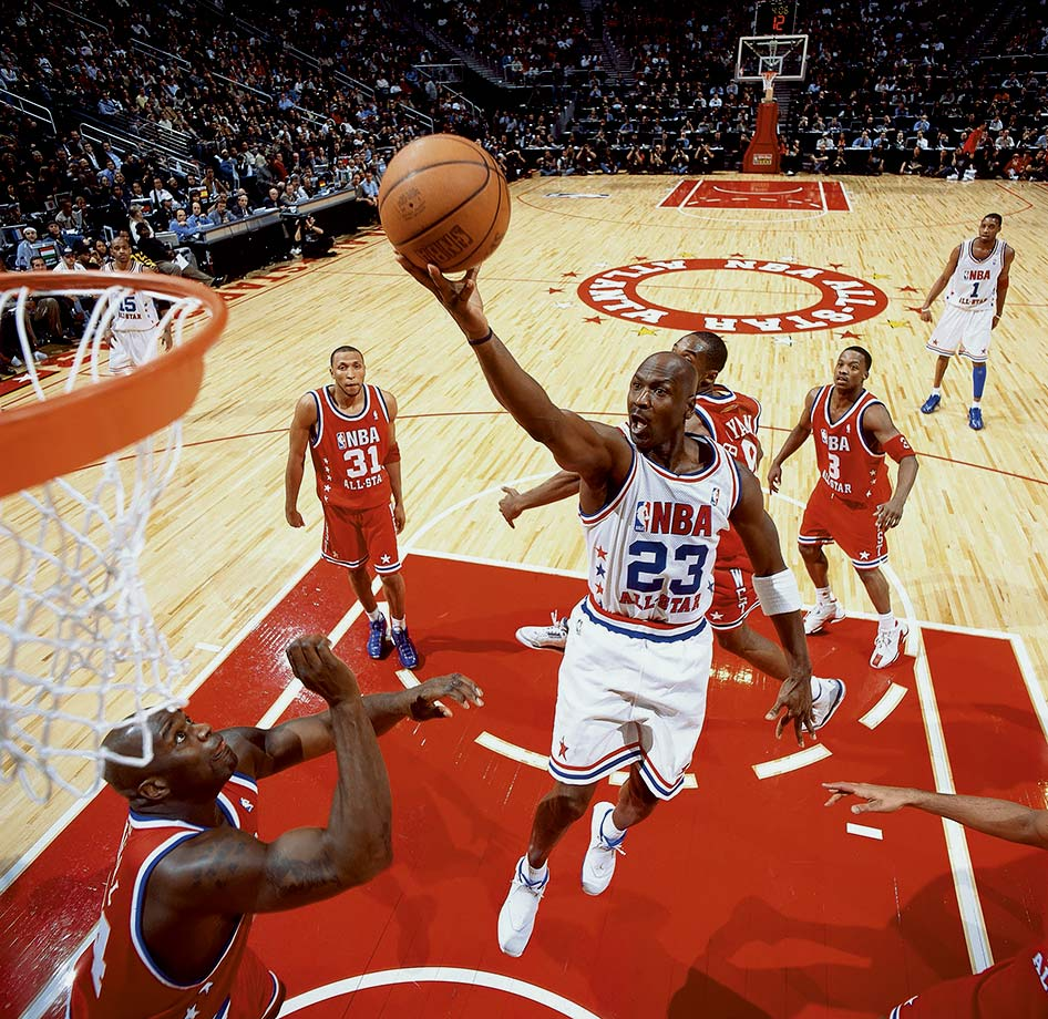 Michael Jordan attacks the basket in his 14th and final All-Star Game in 2003. Jordan started the game when Vince Carter offered him his starting spot, and seemed poised to have the game winner with a baseline jumper with 4.8 seconds remaining in overtime. Instead, Jermaine O'Neal fouled Kobe Bryant to force a second overtime, and the West prevailed.
