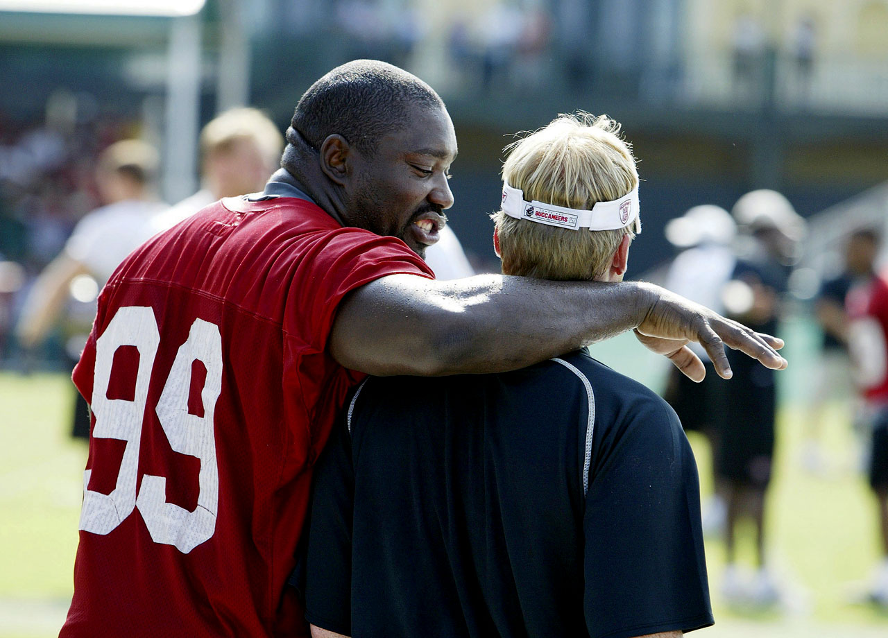 Warren Sapp chats with Bucs head coach Jon Gruden after training camp practice on July 24, 2003 in Lake Buena Vista, Fla.