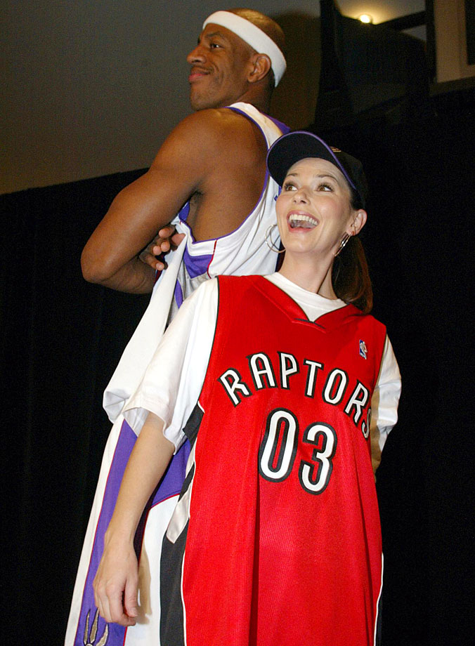 Shania Twain stands back-to-back with Toronto Raptors power forward Jerome Williams as she models a new Raptors jersey design on Oct. 3, 2003 in Toronto.