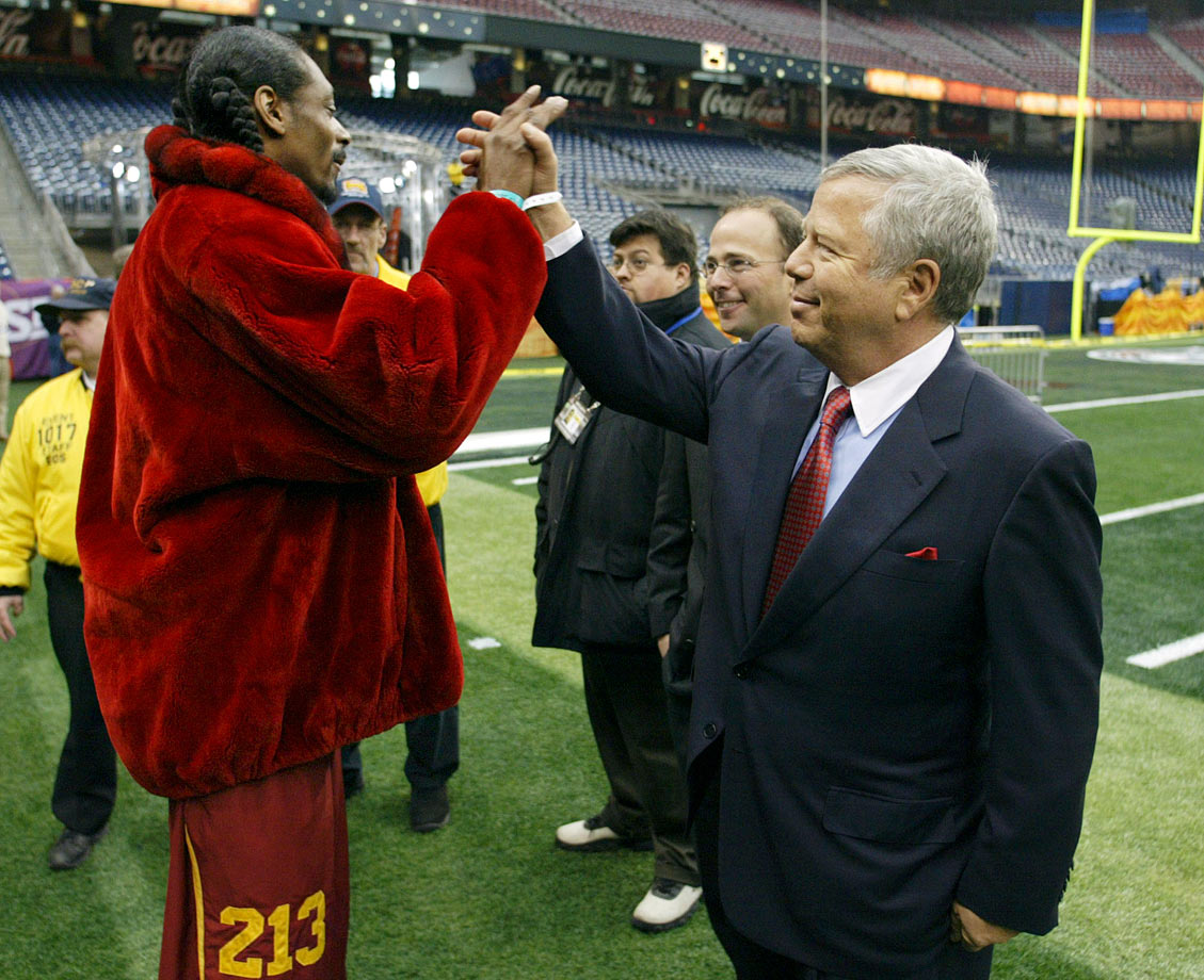 Snoop Dogg gives a high-five to New England Patriots owner Robert Kraft as they check out the field at Reliant Stadium on Jan. 31, 2004 in Houston, Texas.