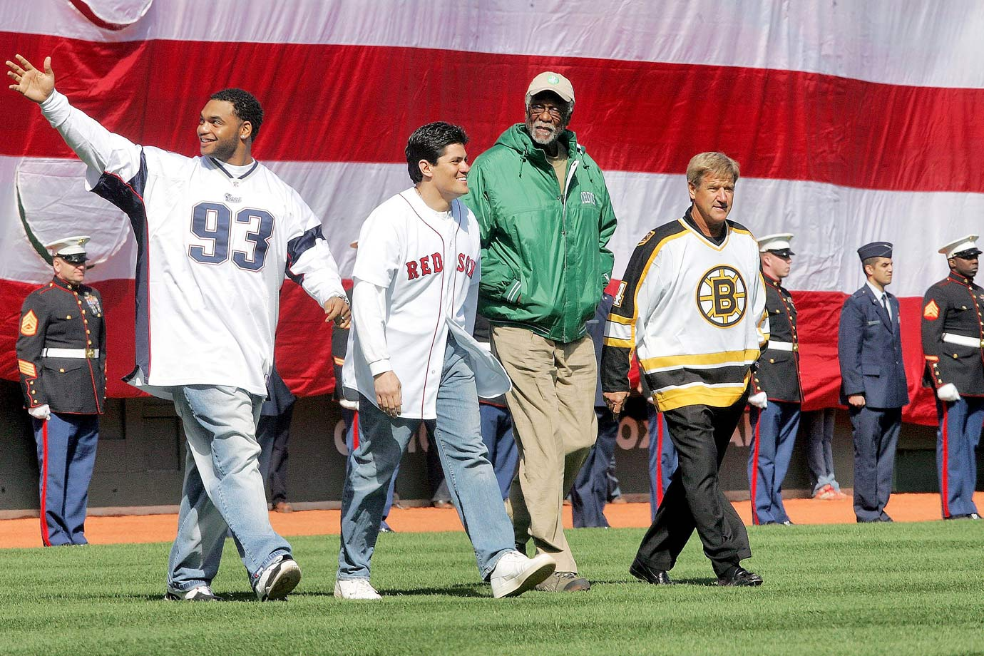 New England Patriots stars Richard Seymour and Tedy Bruschi walk to the mound alongside Bill Russell and Bobby Orr to toss the first pitch before the Red Sox home opener against the Yankees. After the Red Sox banished the Curse of the Bambino the previous fall, the team brought in some of Boston's biggest champions for the ceremony.