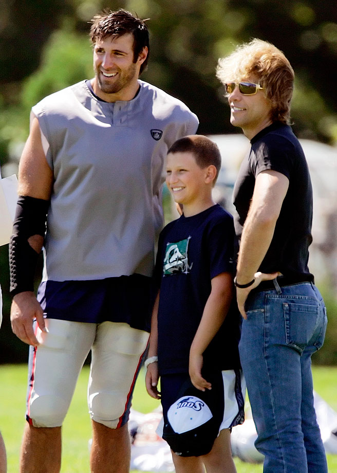 New England Patriots linebacker Mike Vrabel poses with Jon Bon Jovi and his son, Jesse, at the end of the team's morning practice session at their summer football training camp in Foxborough, Mass.