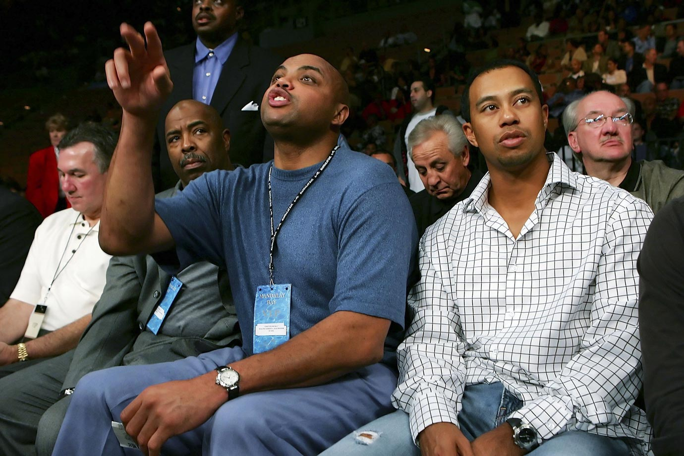 Charles Barkley sits with Tiger Woods during the Robert Guerrero and Orlando Salido IBF Featherweight Championship fight in Las Vegas. Despite Barkley's attempts to learn how to properly swing a golf club, the two are close friends.