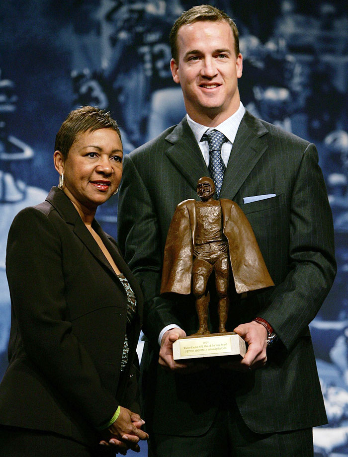 Peyton Manning holds the NFL's Walter Payton Man of the Year trophy alongside Connie Payton at a press conference.
