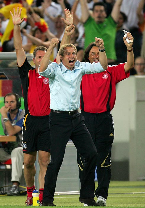 Klinsmann celebrates on the touchline after Bastian Schweinsteiger scores the first goal against Portugal in the third-place game.
