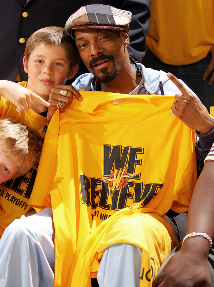 "Snoop Dogg holds up a ""We Believe"" t-shirt with a young fan during Game Six of the Western Conference Quarterfinals between the Golden State Warriors and Dallas Mavericks on May 3, 2007 at Oracle Arena in Oakland, Calif."