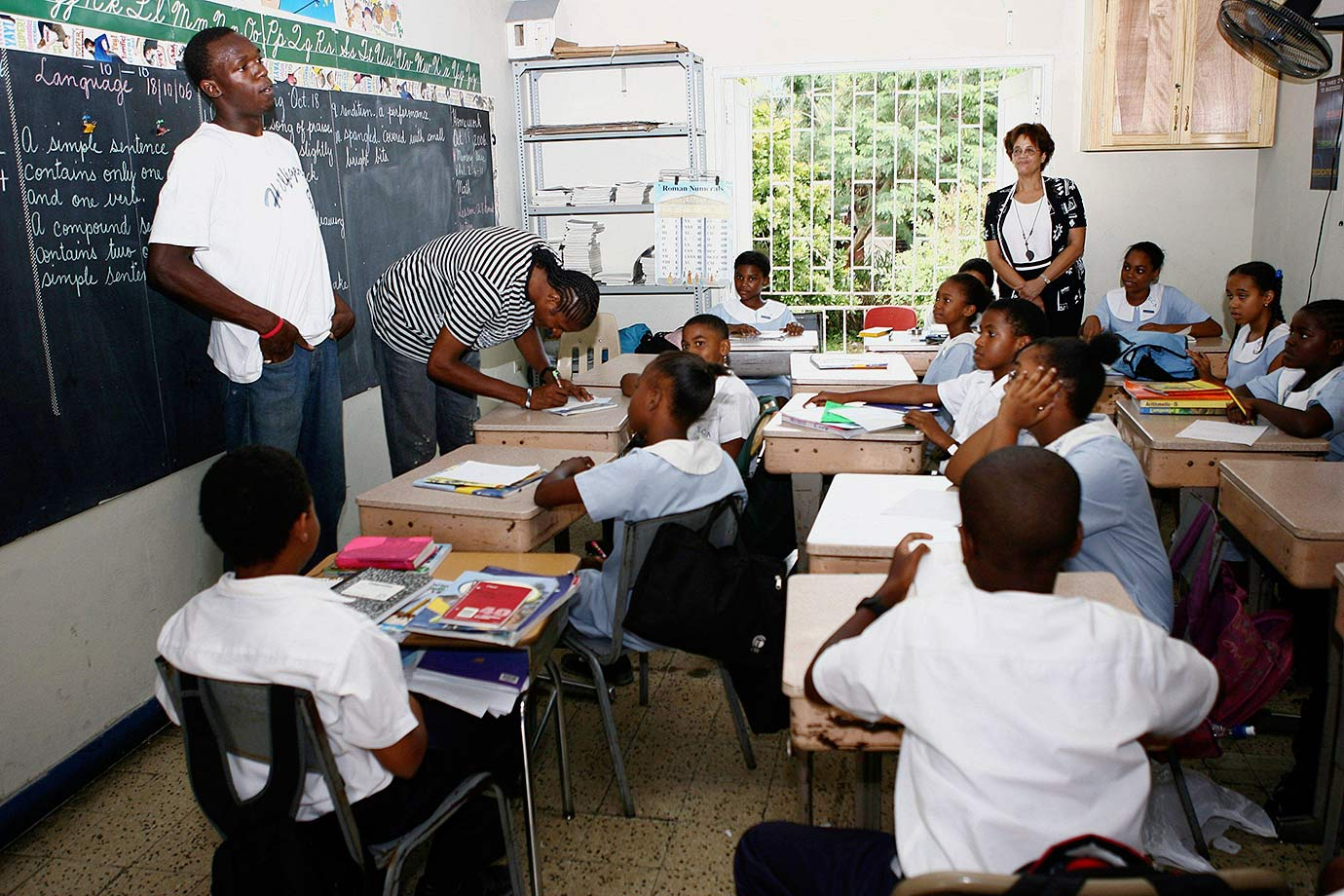 A current resident of Kingston, Jamaica, Bolt is pictured here during a visit to a grade school.