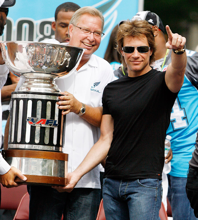 Philadelphia Soul co-owners Ron Jaworski and Jon Bon Jovi hold up the Arena Football League Championship trophy during a public celebration of the team's victory.