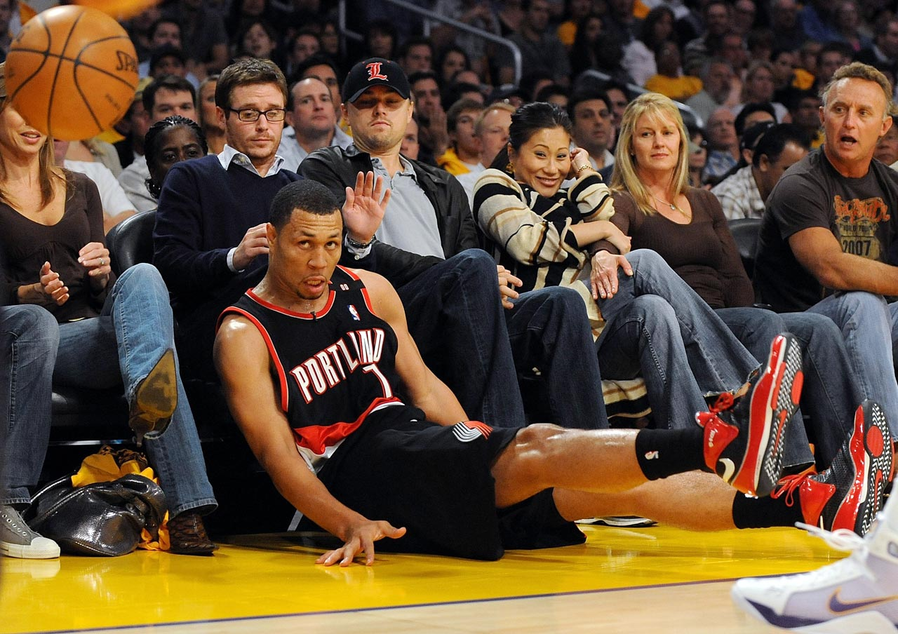 Kevin Connolly and Leonardo Dicaprio react as Brandon Roy falls into the front row during the Los Angeles Lakers game against the Portland Trail Blazers at Staples Center in Los Angeles.