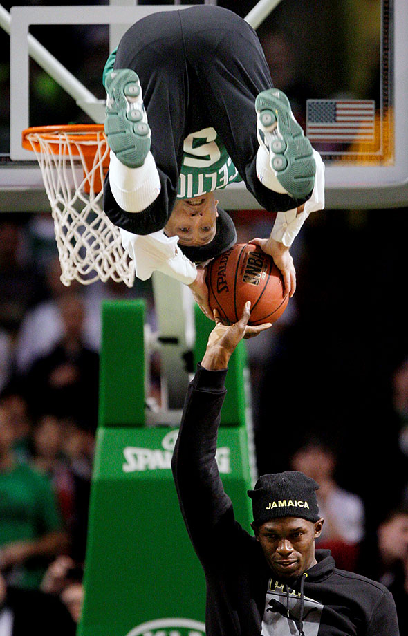 Bolt helps Boston Celtics mascot Lucky perform a trick dunk during a break in the action at a Boston-Chicago game.