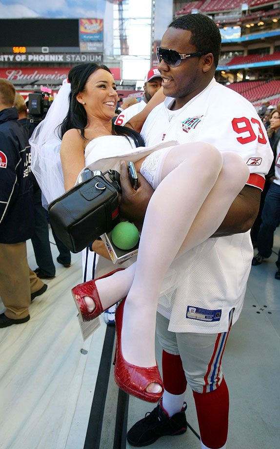 Giants defensive tackle Jay Alfordpicks up TV Azteca's Ines Gomez Mont during Media Day for Super Bowl XLII in Glendale, Ariz.