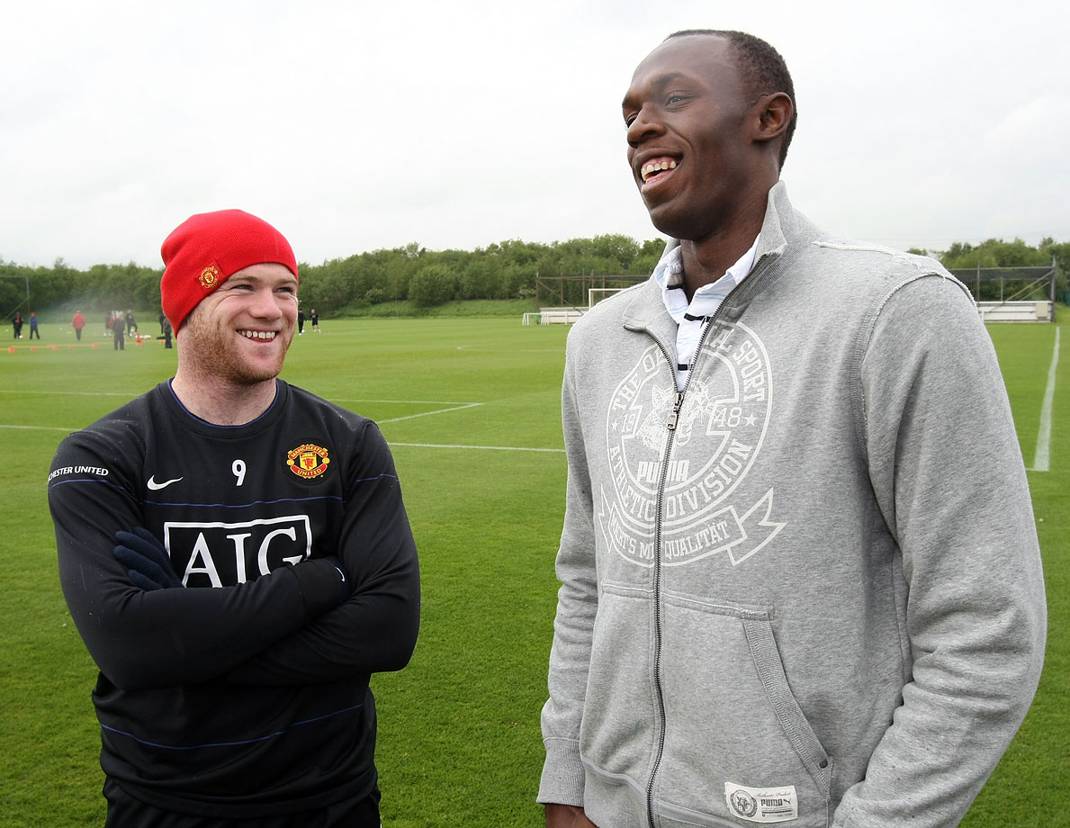 Bolt shares a laugh with Manchester United star Wayne Rooney ahead of a First Team training session at Carrington Training Ground in Manchester, England.