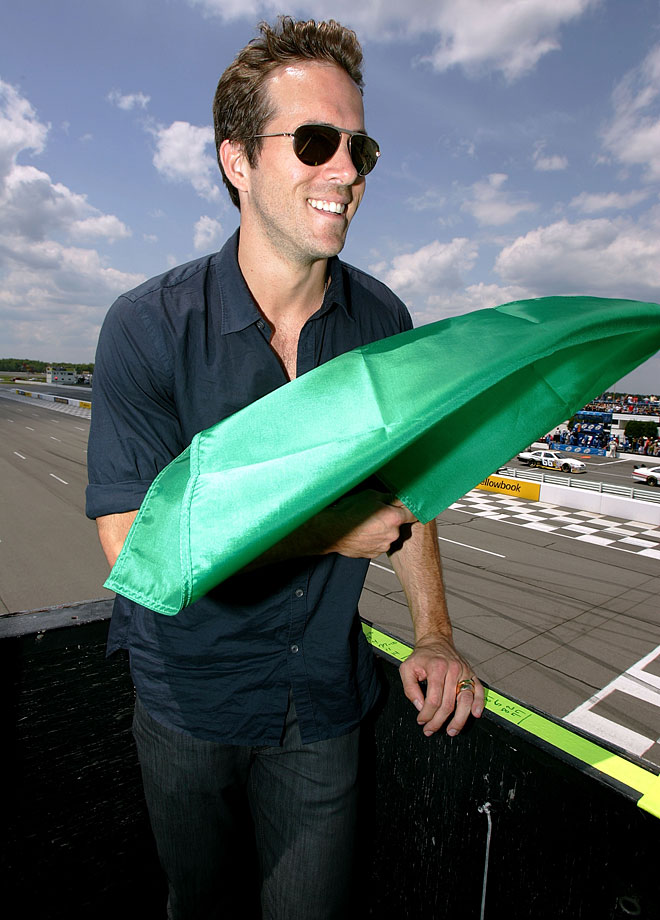 Grand Marshall Ryan Reynolds holds the green flag in the starters' stand before serving as honorary starter during the NASCAR Sprint Cup Series Pocono 500 on June 7, 2009 at Pocono Raceway in Long Pond, Penn.