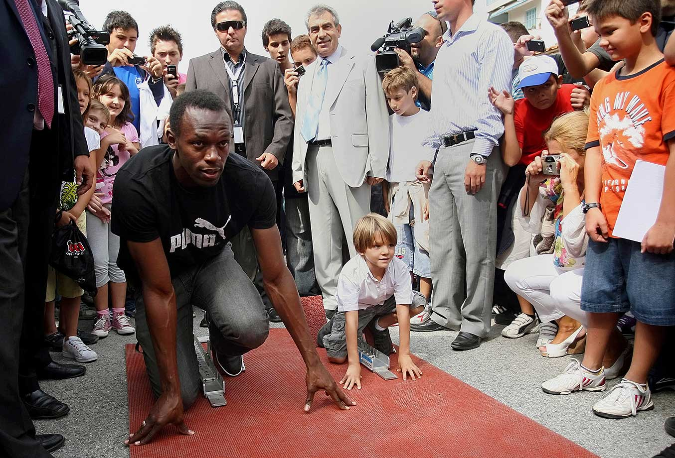 Bolt lines up in a starting position alongside a young boy in Thessaloniki, Greece. Bolt competed in the 200 during the world championships a couple days later, setting a track record of 19.68 and taking home a gold medal.