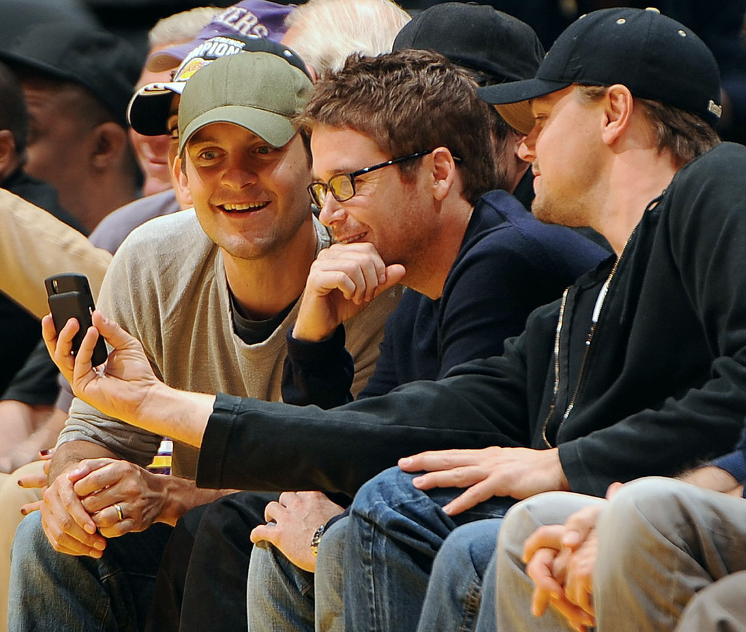 Tobey Maguire and Kevin Connolly look at something on Leonardo DiCaprio's phone during the Los Angeles Lakers game against the New Orleans Hornets at Staples Center in Los Angeles.