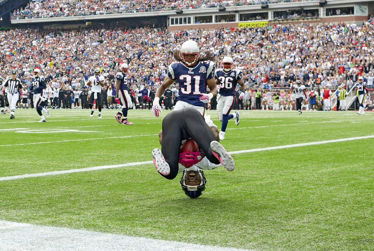 Ravens wideout Derrick Mason rolls over in end zone after making a touchdown catch as Patriots safety Brandon Meriweather watches.