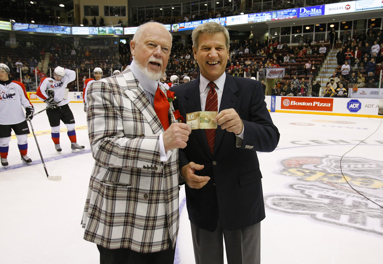 Bobby Orr collects a $100 bet from Don Cherry after the two coached the 2009 Top Prospects Game, the annual showcase for top junior talent. Orr's team won the game 6-1.