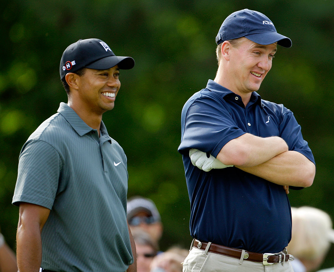Peyton Manning shares a laugh with Tiger Woods during the pro-am of the Quail Hollow Championship golf tournament in Charlotte, N.C.