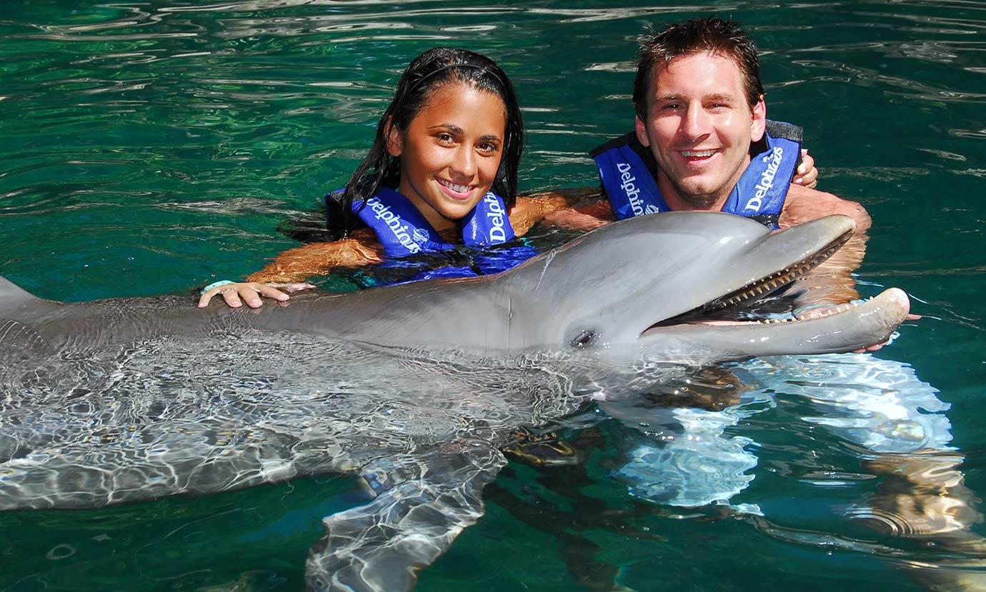 Lionel Messi and girlfriend Antonella Rocuzzo swim with dolphins at the Delphinus aquarium on July 24, 2010 in Playa del Carmen, Mexico.