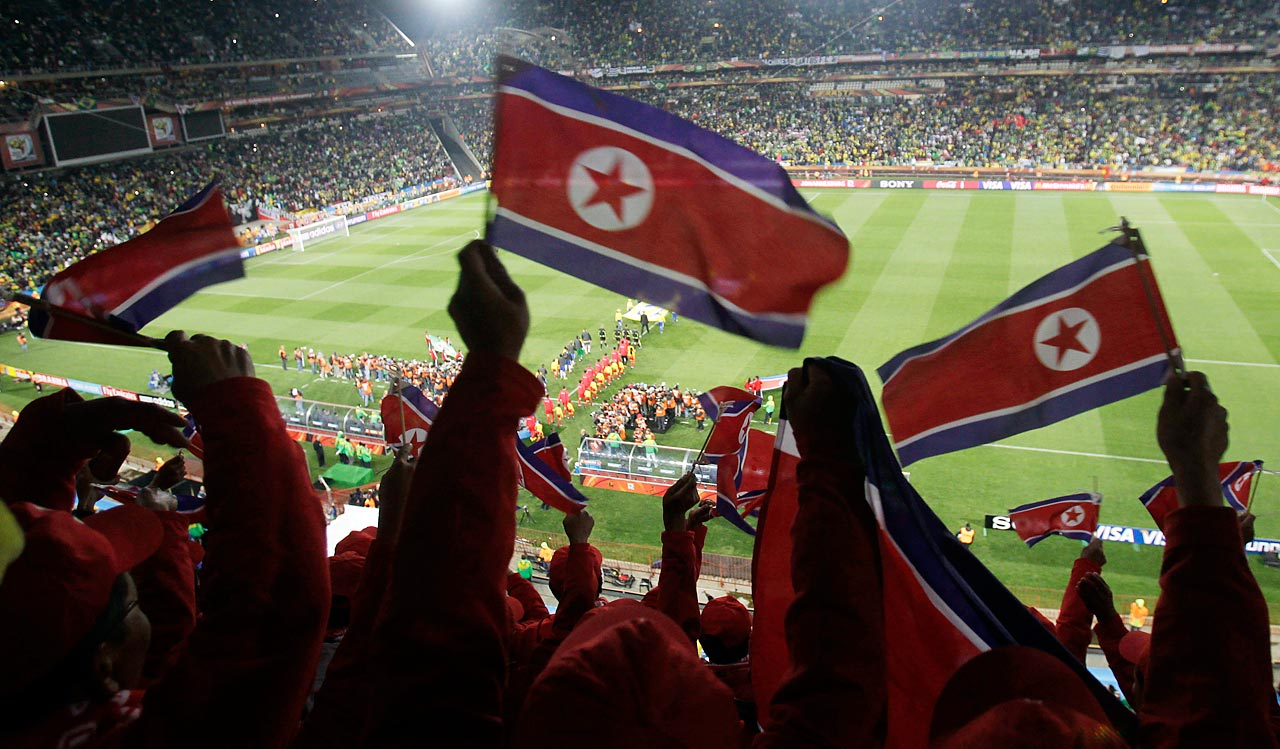 North Korea supporters wave the national flag as North Korea walks onto the pitch with their opponents, Brazil, ahead of their Group G matchup in the 2010 World Cup.