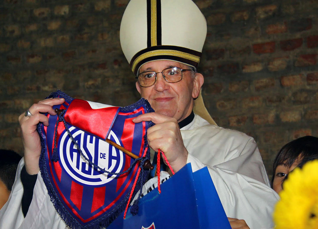 Argentina's Cardinal Jorge Mario Bergoglio (now Pope Francis) poses with the San Lorenzo team emblem, which he supports in Buenos Aires, on May 24, 2011.