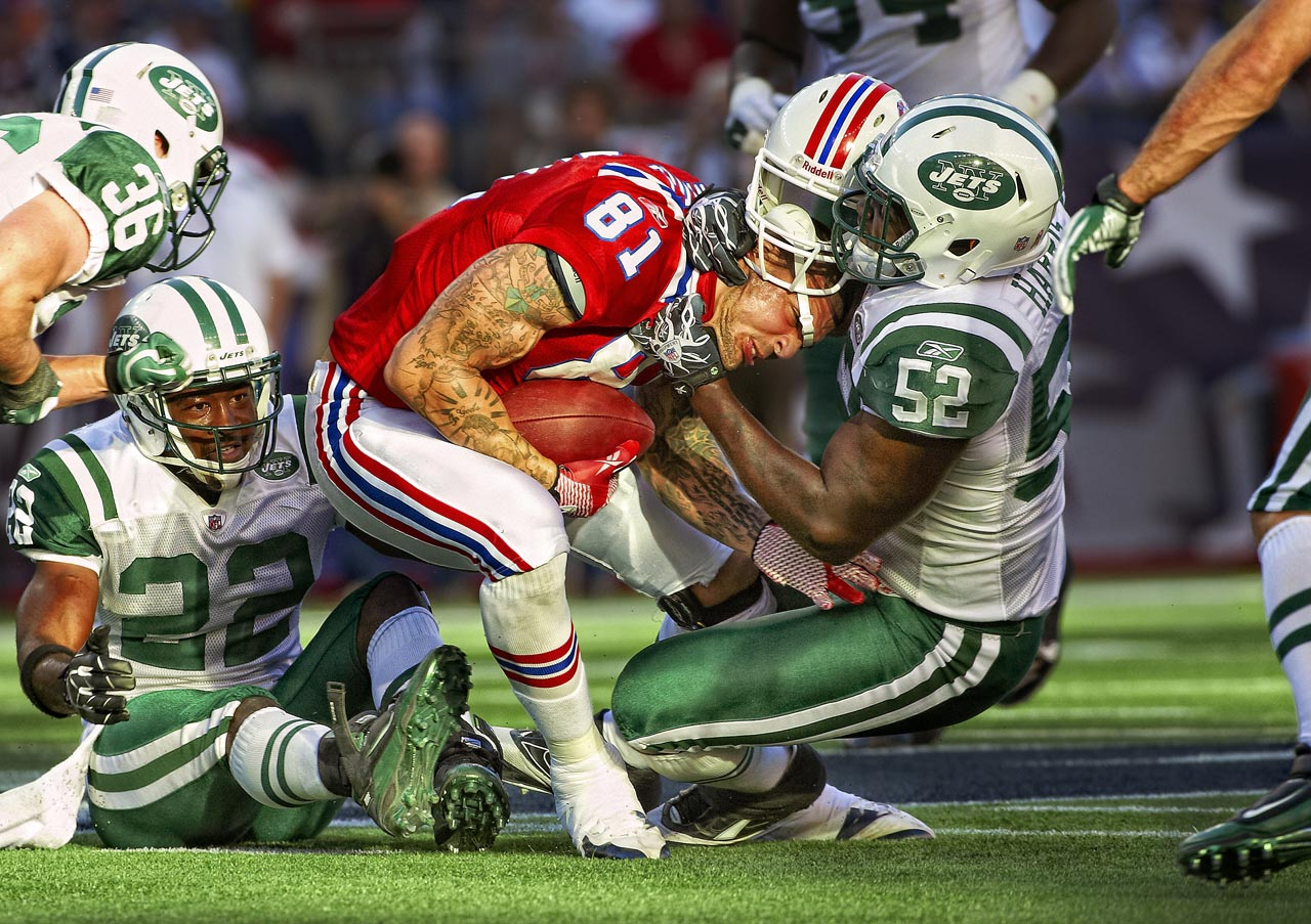 Jets linebacker David Harris rips the helmet off Patriots tight end Aaron Hernandez as he makes the tackle.
