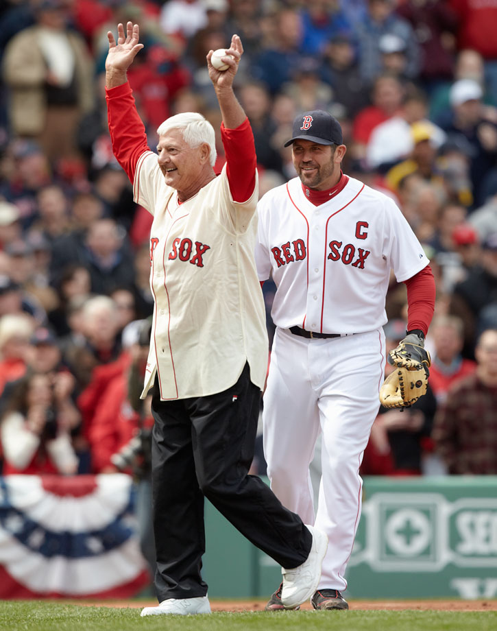 Carl Yastrzemski waves to the crowd as Red Sox catcher Jason Varitek looks on during the ceremonial first pitch before a game against the New York Yankees on April 9, 2011 at Fenway Park in Boston.