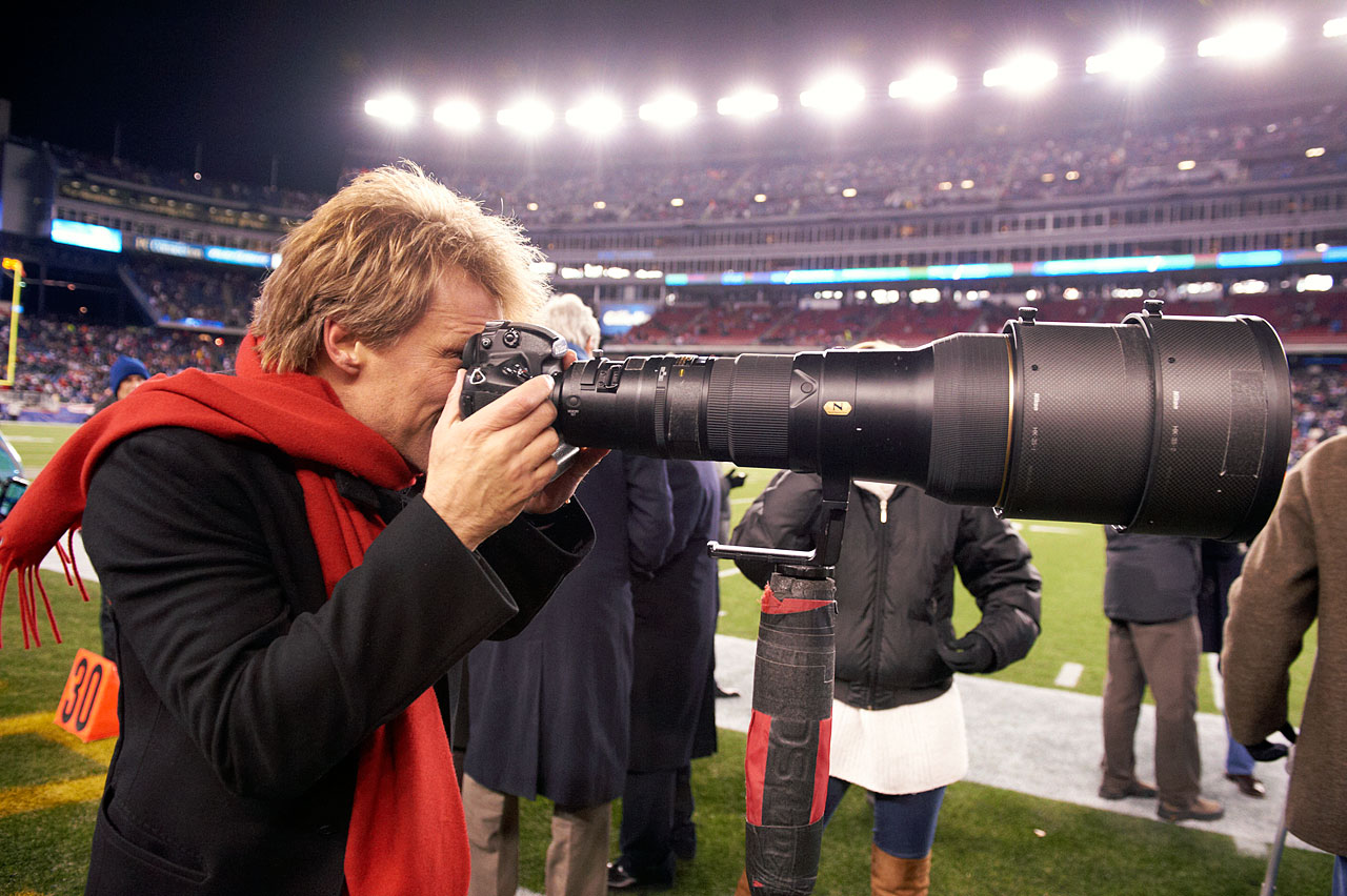 Jon Bon Jovi tries out a telescopic lens and camera during the AFC Divisional Playoff game between the Denver Broncos and New England Patriots at Gillette Stadium in Foxborough, Mass.