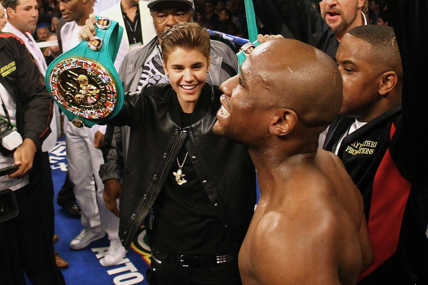 Justin Bieber holds up Floyd Mayweather Jr.'s title belts before Mayweather's WBA super welterweight title fight against Miguel Cotto on May 5, 2012 at the MGM Grand Garden Arena in Las Vegas.
