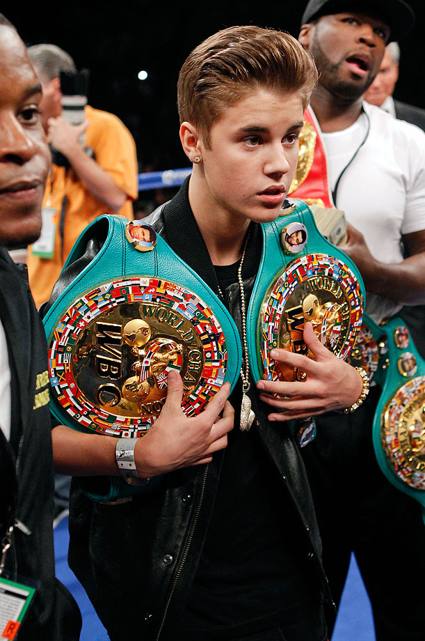 Justin Bieber carries Floyd Mayweather Jr.'s title belts into the ring before Mayweather's WBA super welterweight title fight against Miguel Cotto on May 5, 2012 at the MGM Grand Garden Arena in Las Vegas.