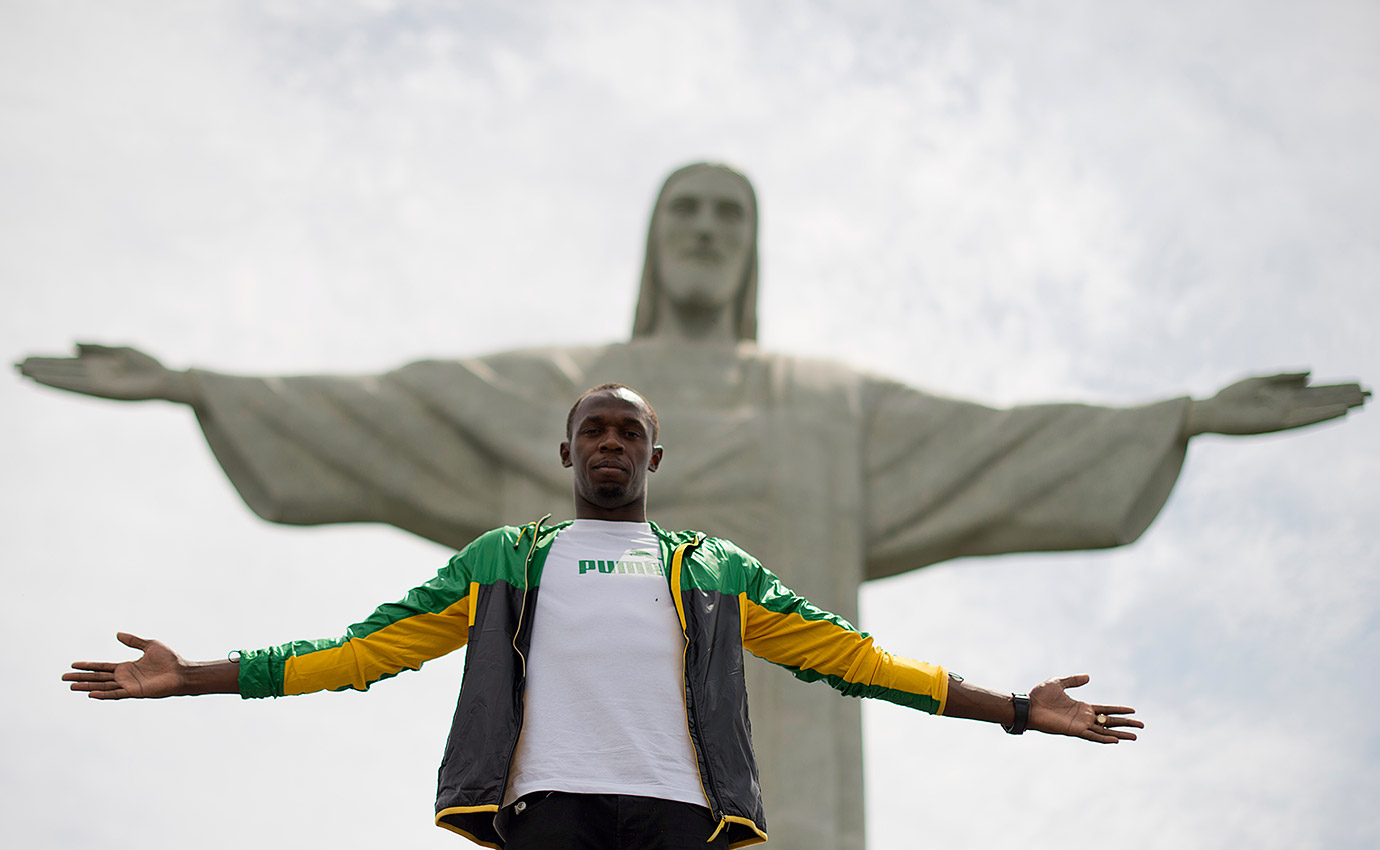 Bolt poses under the Christ the Redeemer statue on Corcovado Mountain in Rio de Janeiro, Brazil.