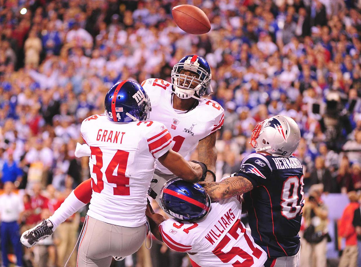 Giants defenders Kenny Phillips (21), Jacquian Williams (57) and Deon Grant (34) break up a Hail Mary pass intended for Patriots tight end Aaron Hernandez.