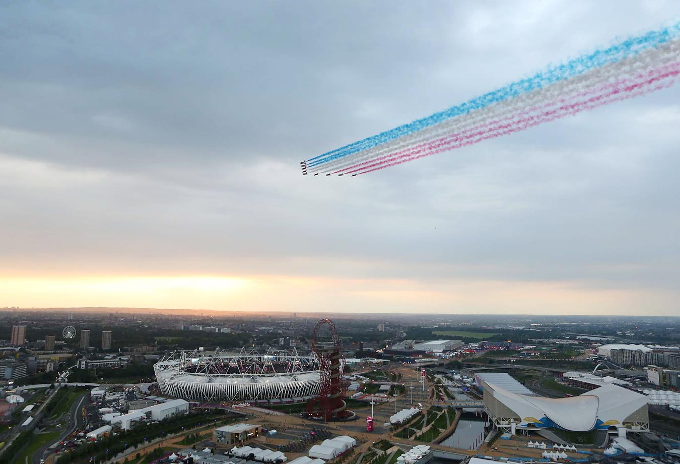 The Royal Air Force aerobatic team, the Red Arrows, performs a flyover at the Olympic Stadium during the Opening Ceremony of the 2012 London Summer Games.