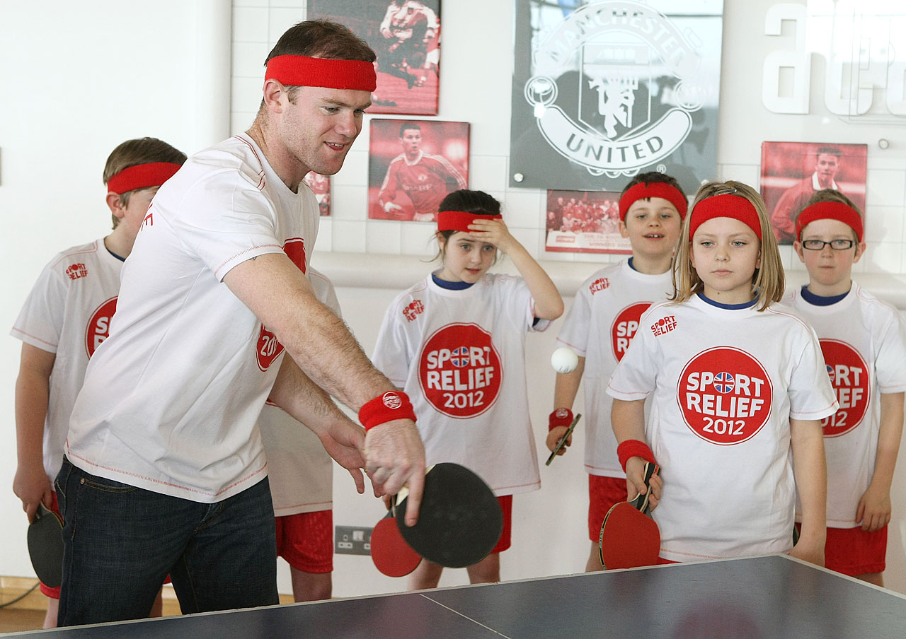 Rooney plays table tennis with local school children on behalf of Sports Relief at Carrington Training Ground on March 13, 2012 in Manchester, England.