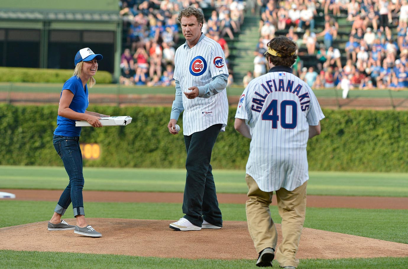 Will Ferrell looks to Zach Galifianakis for money to pay a pizza delivery girl prior to throwing out the first pitch for the Chicago Cubs game against the Florida Marlins on July 18, 2012 at Wrigley Field in Chicago.