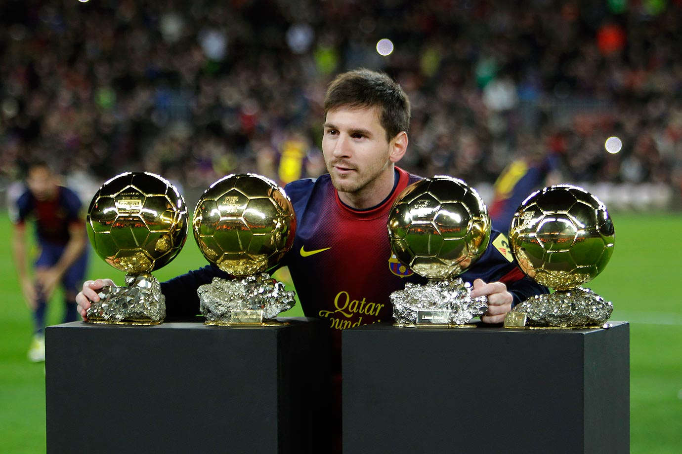 Barcelona's Lionel Messi poses with his four FIFA Men's World Player of the Year awards before a Copa del Rey match against Malaga on Jan. 16, 2013 at the Camp Nou stadium, in Barcelona, Spain. Messi received the award for a record-breaking fourth successive year.