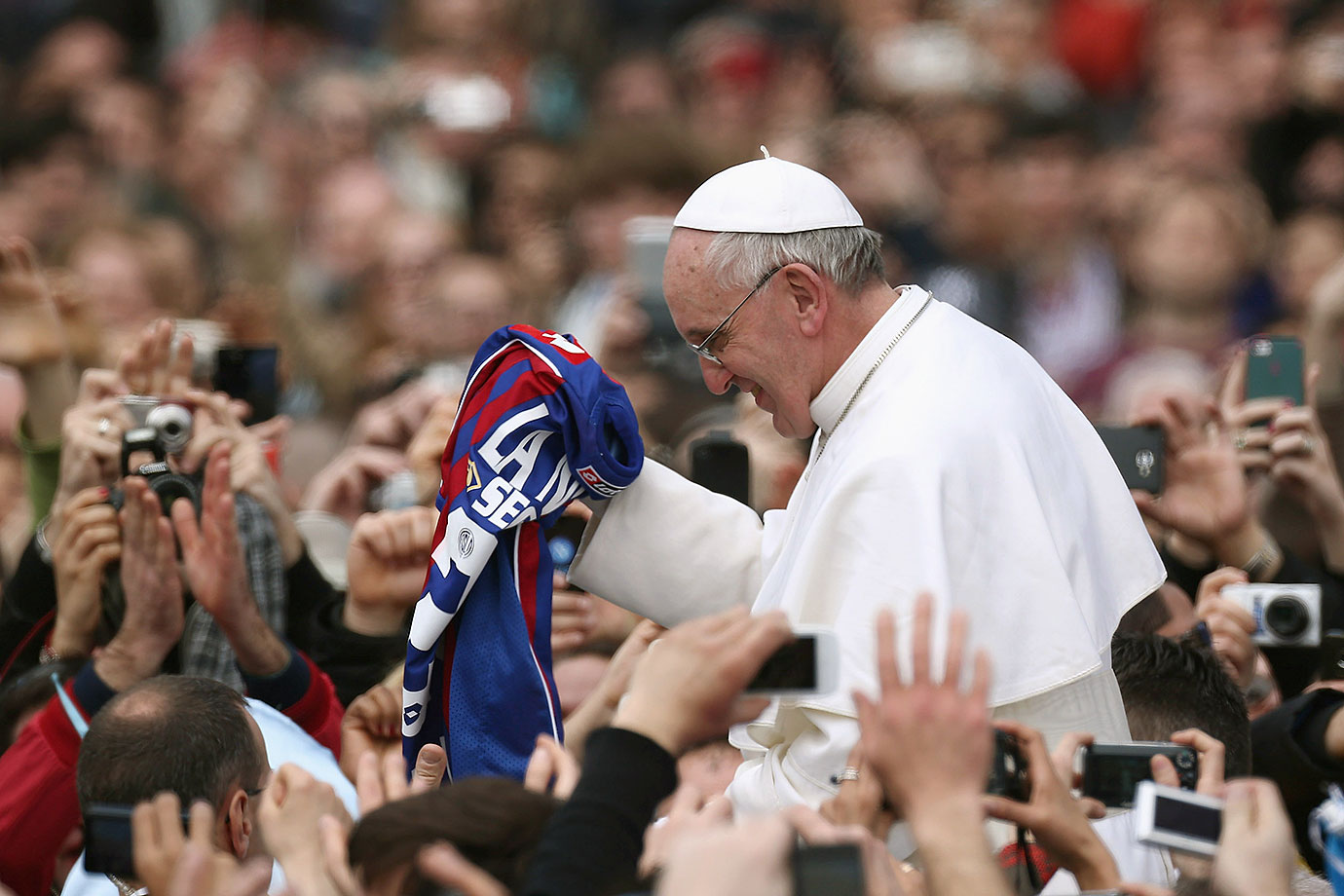 Pope Francis is given a San Lorenzo jersey as he greets the faithful prior to his first 'Urbi et Orbi' blessing from the balcony of St. Peter's Basilica during Easter Mass on March 31, 2013 in Vatican City.