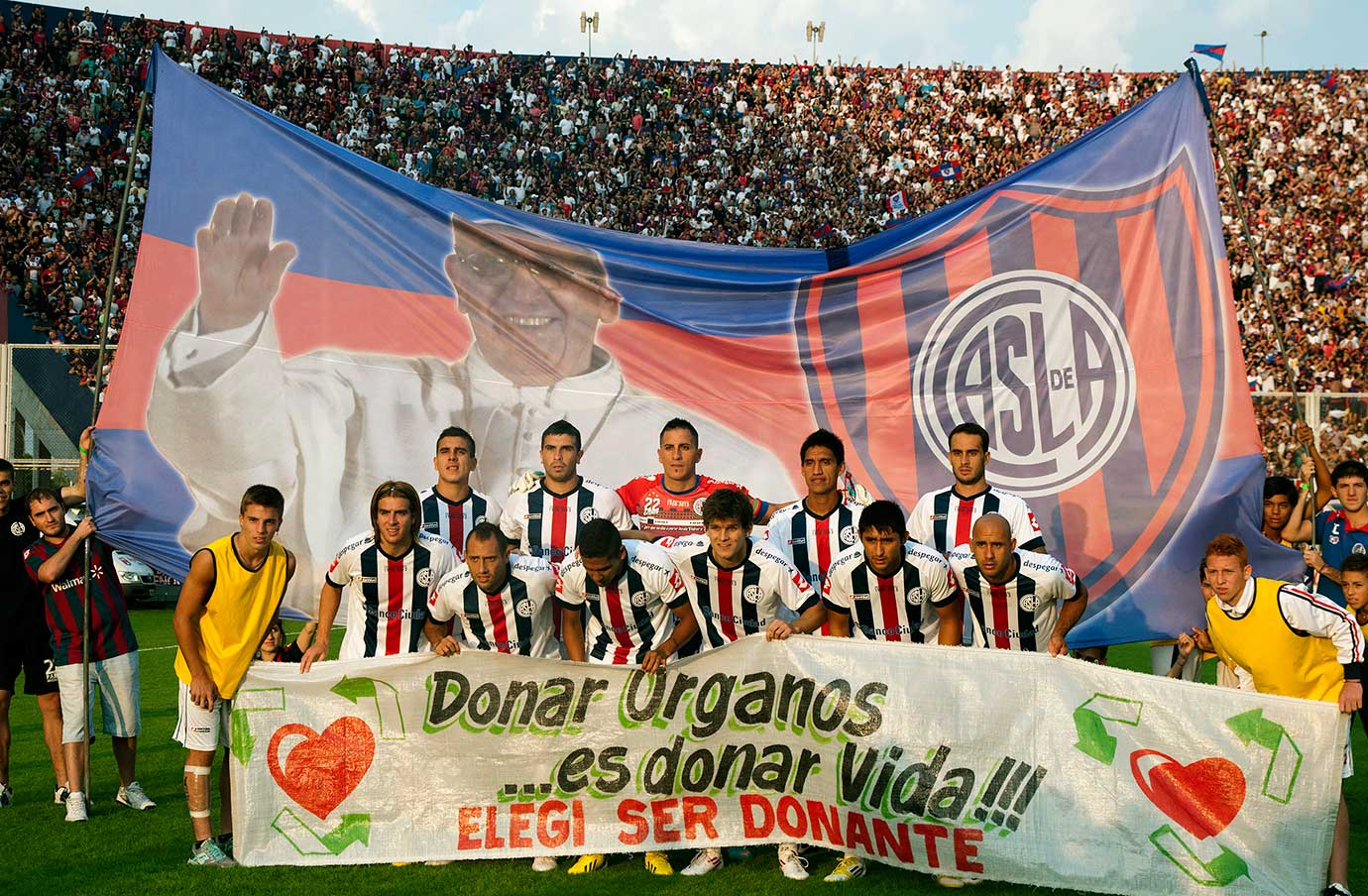 Argentina's San Lorenzo team poses with a huge flag behind them with an image of Pope Francis before the start of their match against Newell's Old Boys on March 31, 2013 in Buenos Aires.