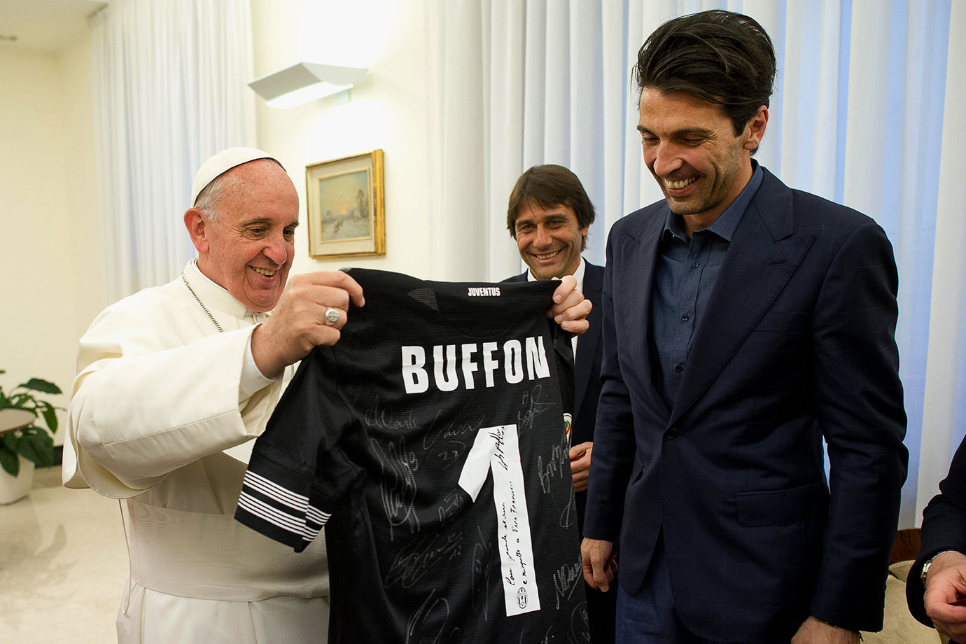 Pope Francis receives an autographed Juventus jersey from captain Gianluigi Buffon (right) and coach Antonio Conte at the end of their audience at The Vatican on May 21, 2013 in Vatican City.