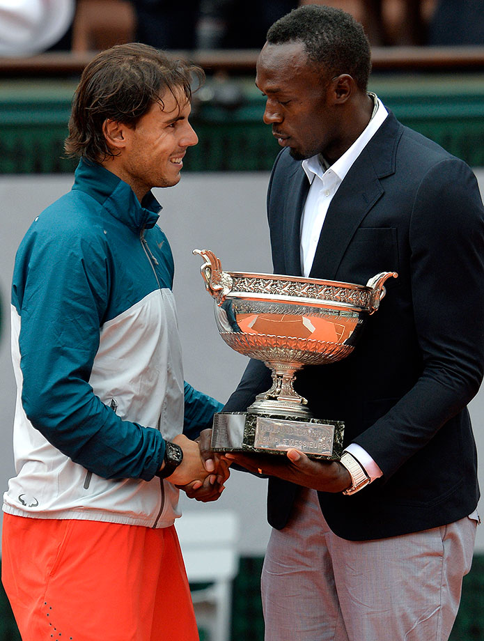 Usain Bolt hands the Musketeers Trophy to 2013 French Open winner Rafael Nadal. With the win, the Spaniard became the first player to capture eight Grand Slam titles at the same event.