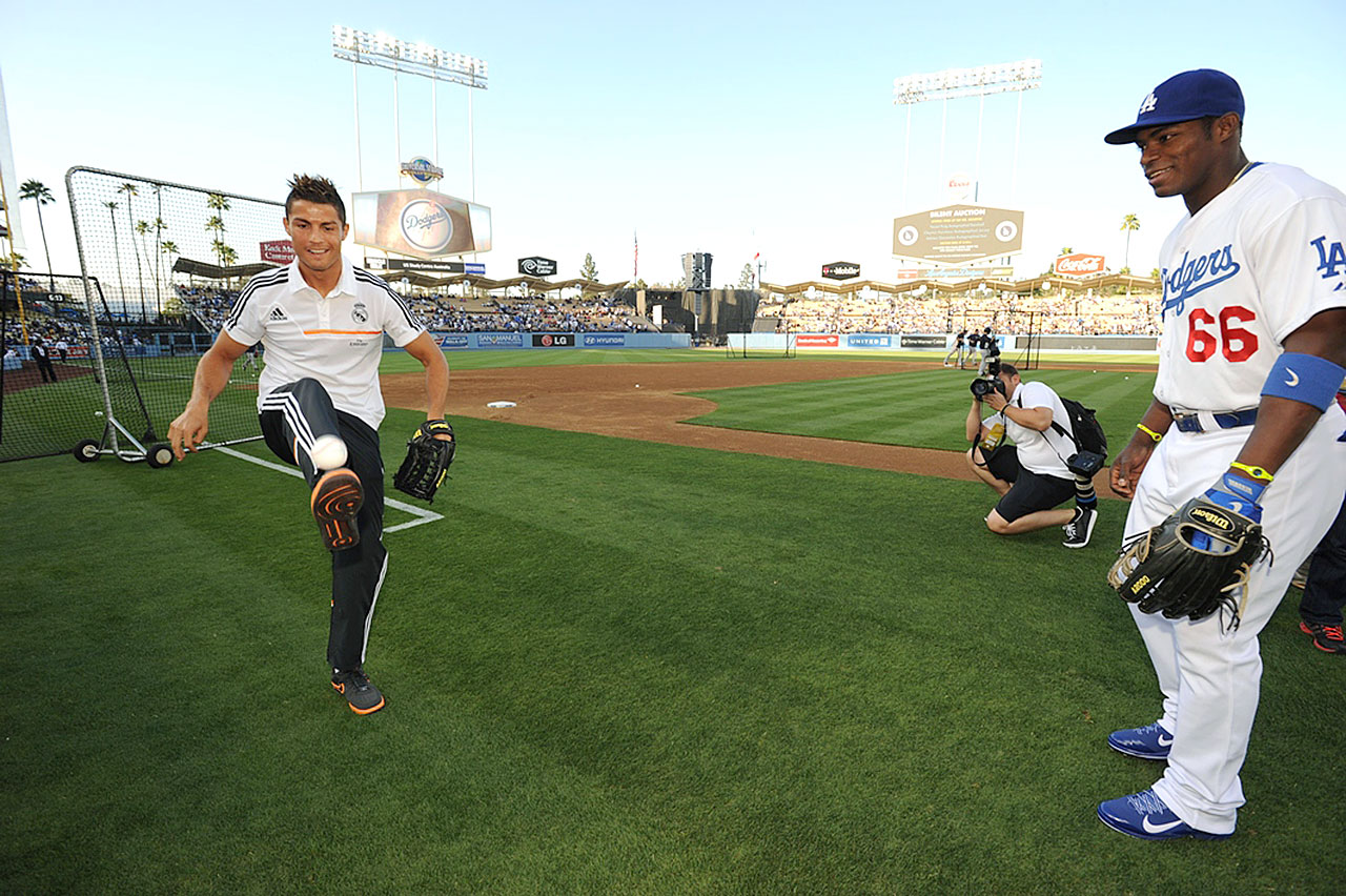 Real Madrid's Cristiano Ronaldo kicks around a baseball as Dodgers outfielder Yasiel Puig looks on prior to the Dodgers game against the New York Yankees at Dodger Stadium in Los Angeles.