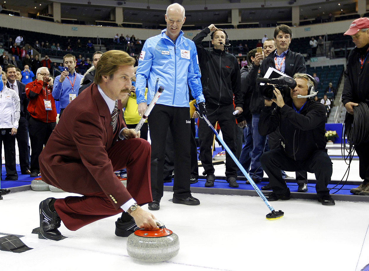 Will Ferrell, as Ron Burgundy, receives instructions from Skip Glenn Howard prior to the start of the Roar of the Rings Canadian Olympic Curling Trials on Dec. 1, 2013 in Winnipeg, Canada.