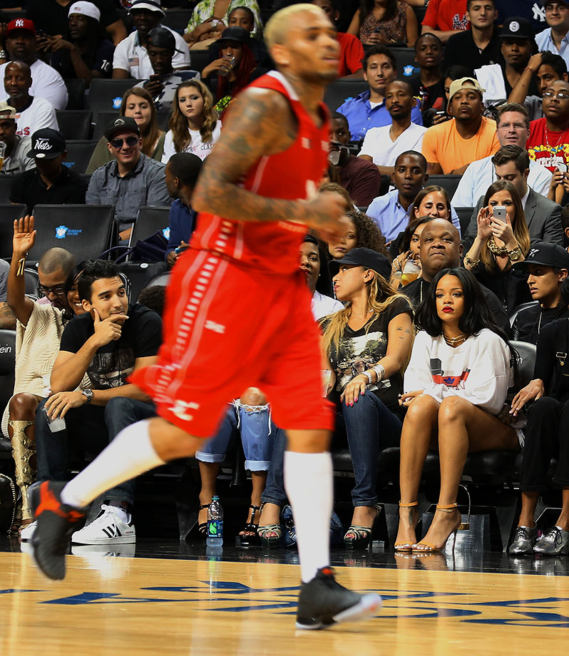 Rihanna looks on as Chris Brown plays in the Summer Classic Charity Basketball Game on Aug. 21, 2014 at the Barclays Center in the Brooklyn borough of New York City.