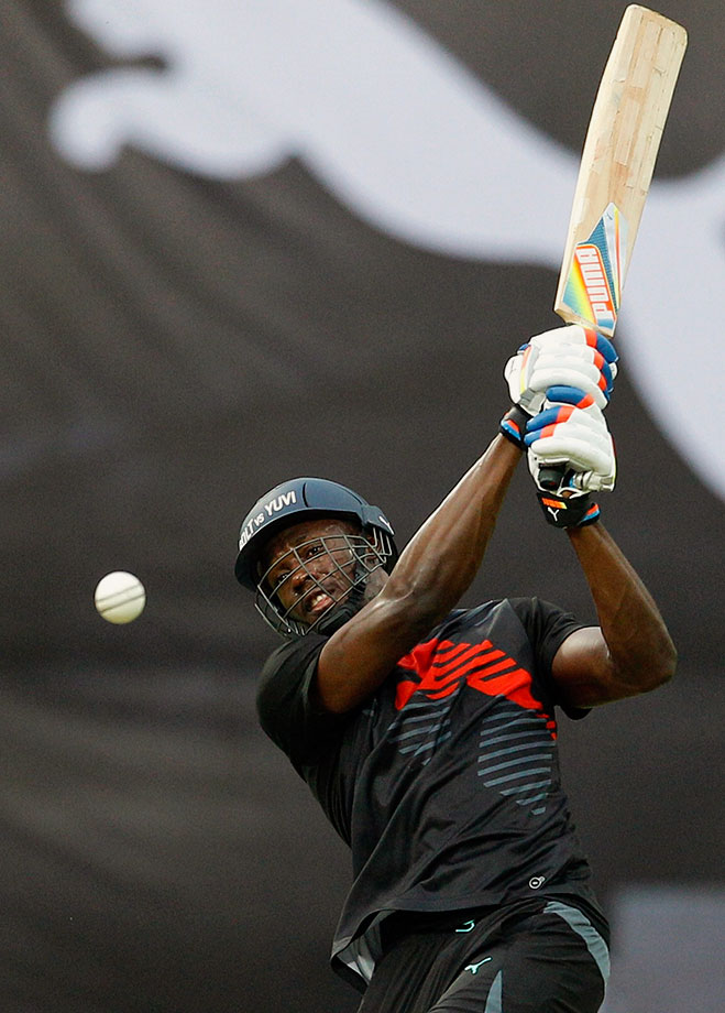Bolt hits a boundary during a friendly cricket match against Indian cricketer Yuvraj Singh's team in Bangalore, India. Bolt's team won the match.