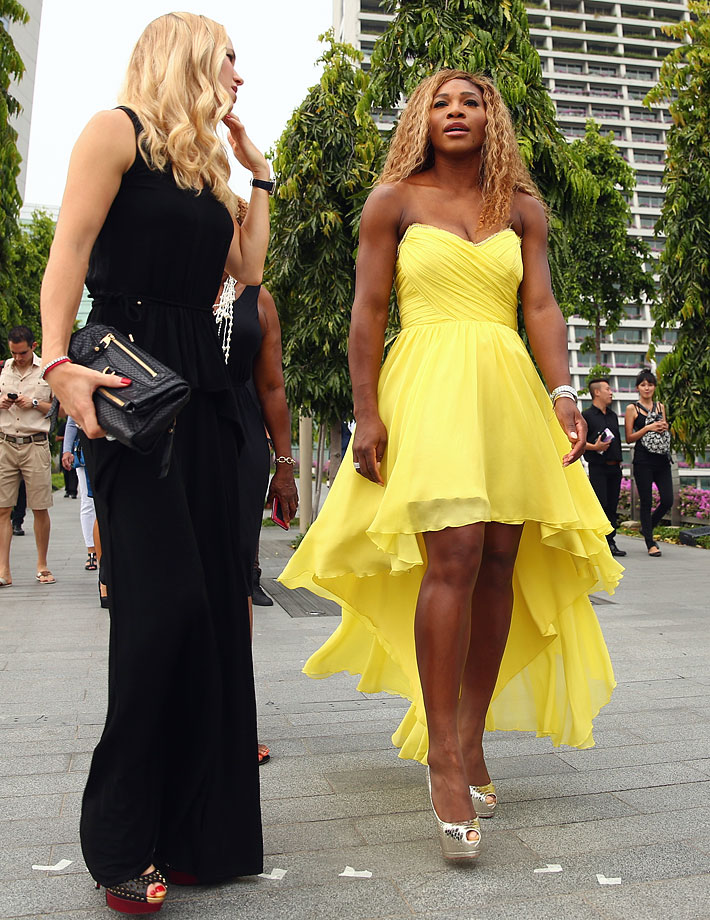 Caroline Wozniacki and Serena Williams walk from the Marina Bay Sands Hotel to the draw ceremony prior to the start of the BNP Paribas WTA Finals at Singapore Sports Hub on Oct. 18, 2014 in Singapore.