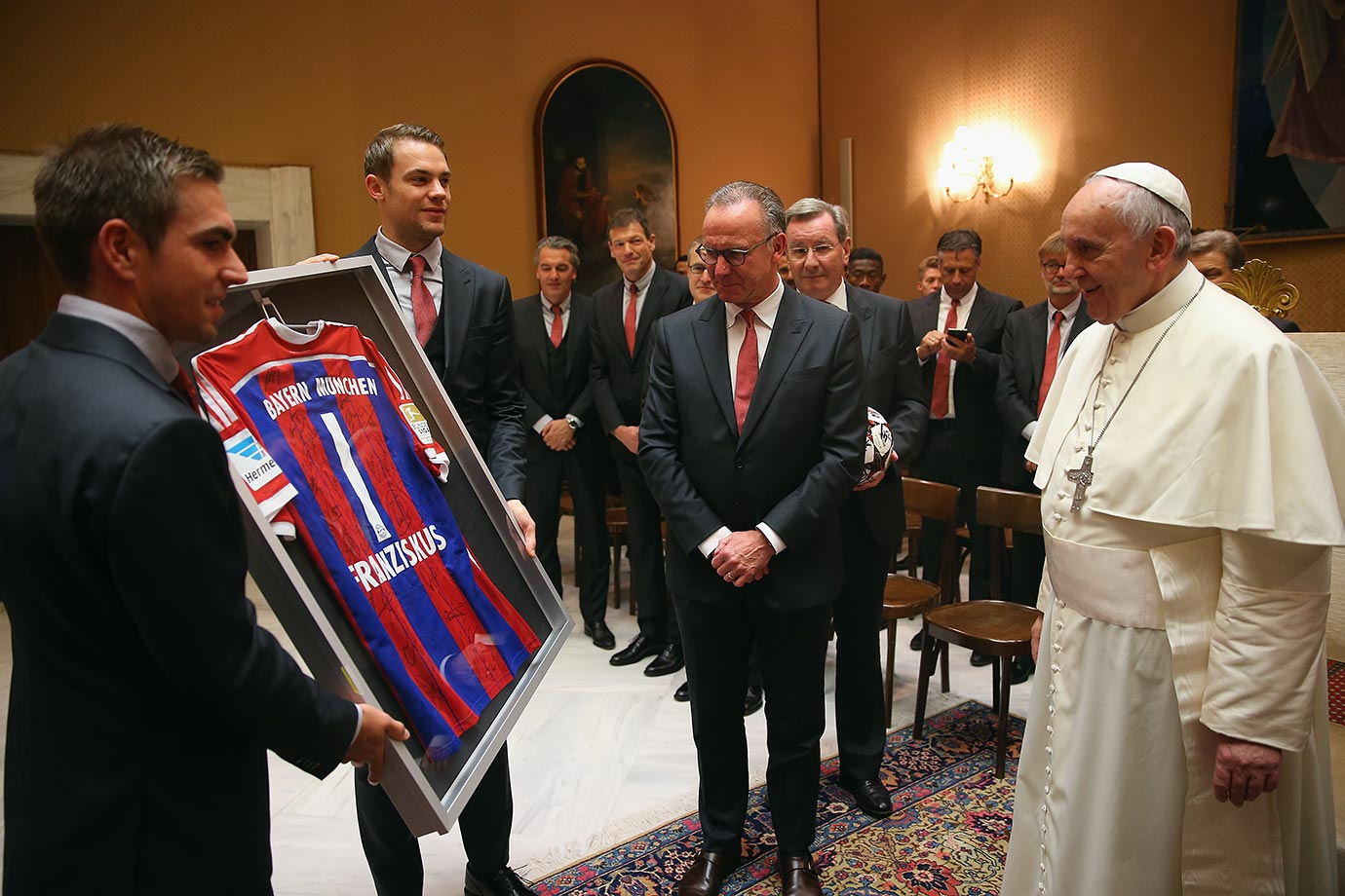 (From left) Philipp Lahm, Manuel Neuer and CEO Karl-Heinz Rummenigge of FC Bayern Muenchen present Pope Francis a team jersey during a private audience at The Vatican October 22, 2014 in Vatican City.