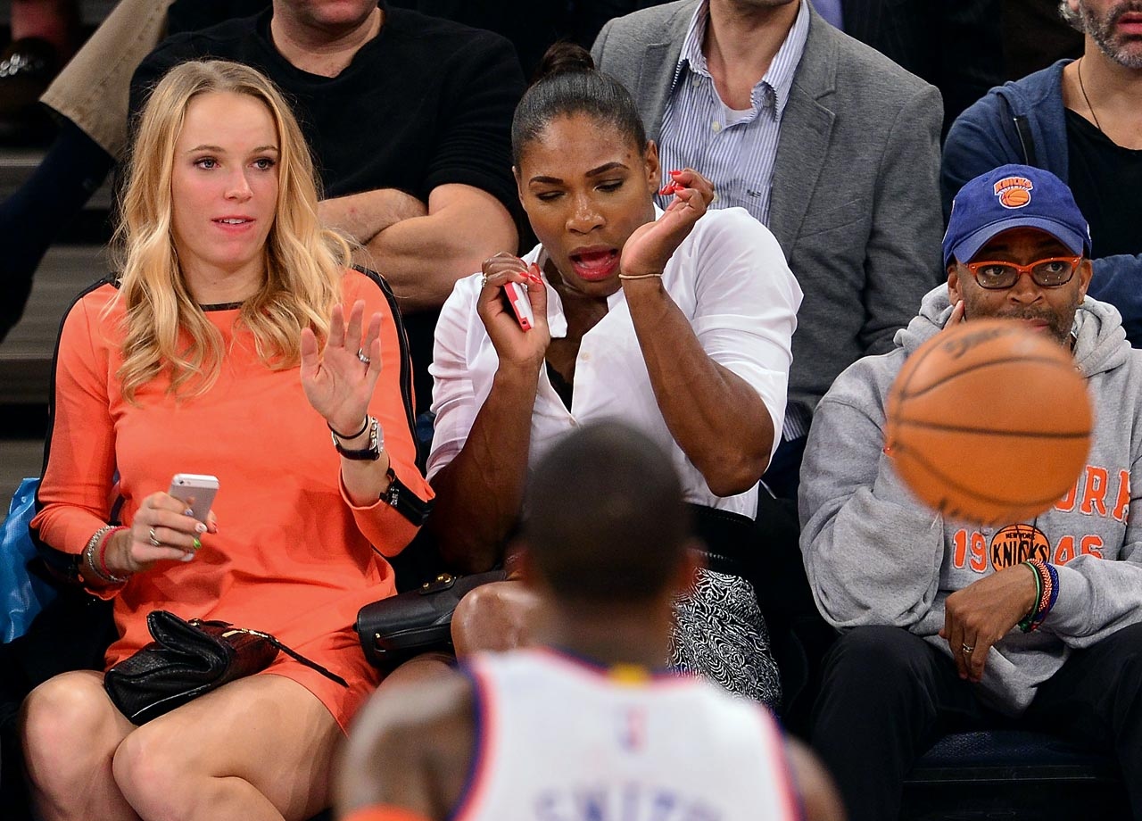 Caroline Wozniacki and Serena Williams flinch at a loose ball as Spike Lee looks on during the New York Knicks game against the Washington Wizards at Madison Square Garden on Nov. 4, 2014 in New York City.
